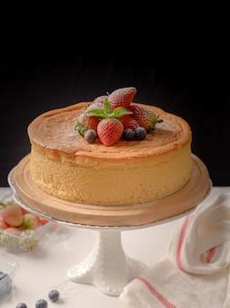 De gelukkige kaastaart van het verjaardags verse fruit met gelukkige verjaardag op cakeconcept met het fruitcake van de aardbeikiwi. voedsel concept.
