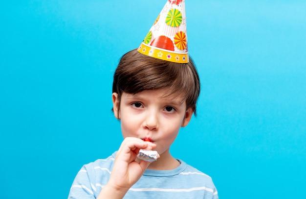 De gelukkige kaukasische jongen viert zijn verjaardag blazend een fluitje op een blauwe muur. vakantie en feest concept met ruimte voor tekst.