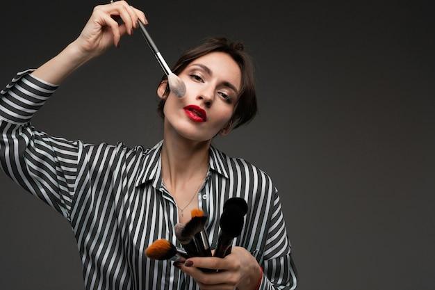 De gelukkige kaukasische vrouw doet make-up met borstels geïsoleerd op grijze muur
