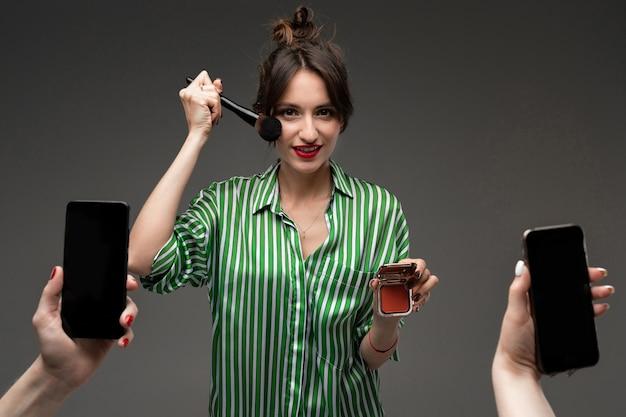 De gelukkige kaukasische vrouw doet make-up met borstels voor spiegel die op grijze muur wordt geïsoleerd