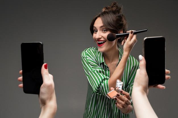 De gelukkige kaukasische vrouw doet make-up met borstels voor spiegel en neemt foto's die op grijze muur worden geïsoleerd