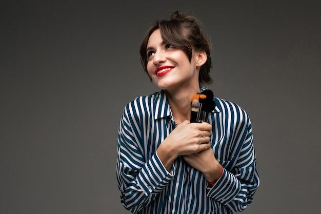 De gelukkige kaukasische vrouw houdt make-upborstels die op grijze muur worden geïsoleerd