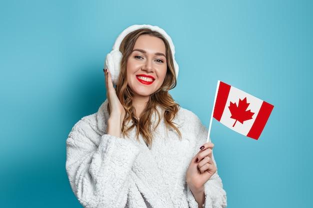 De gelukkige kaukasische vrouw met rode lippen in een faux witte bontjas glimlacht en houdt een kleine canadese vlag die over blauwe muur wordt geïsoleerd