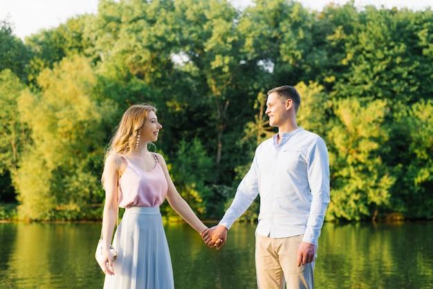 De gelukkige kerel en het meisje glimlachen en houden handen