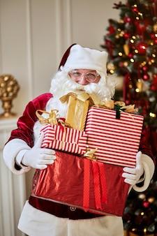De gelukkige kerstman bracht veel cadeaus voor kinderen. vrolijk kerstfeest vakantie concept