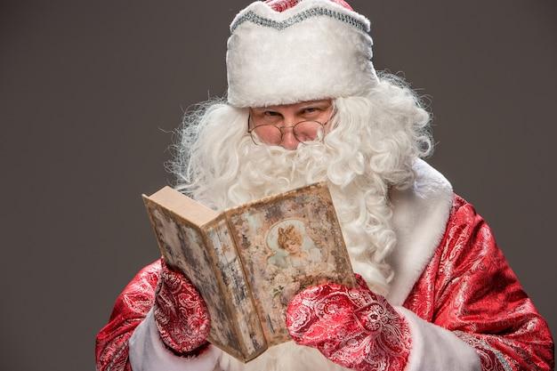 De gelukkige kerstman die in brillen oud boek op donkere achtergrond leest