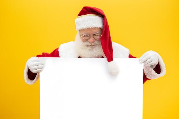 De gelukkige kerstman die uit van achter het lege teken kijkt dat op gele achtergrond met exemplaarruimte wordt geïsoleerd