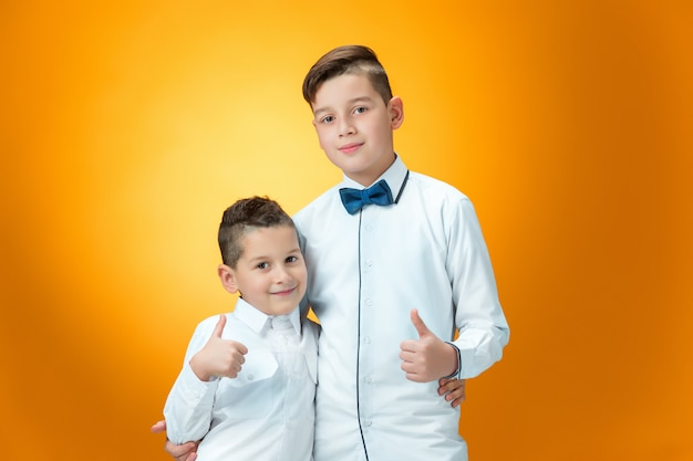 De gelukkige kinderen die duimen tonen ondertekenen omhoog ok