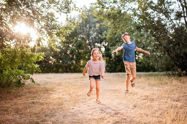De gelukkige kinderenjongen en het meisje stoeien in het park. de oudere broer speelt met zijn zus in de natuur in de zonsondergangstralen van een zomerse dag.