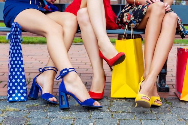 De gelukkige kleurrijke benen van de meisjesvrienden van vrouwenvrouwen volwassenen in het kleurrijke kleding zitten openlucht na het winkelen in winkelcomplex