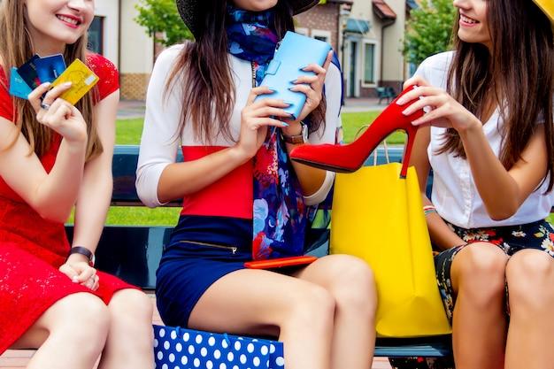 De gelukkige kleurrijke vrienden van de volwassenenmeisjes van vrouwenvrouwen in hoeden en het kleurrijke kleding zitten openlucht na het winkelen in winkelcomplex.