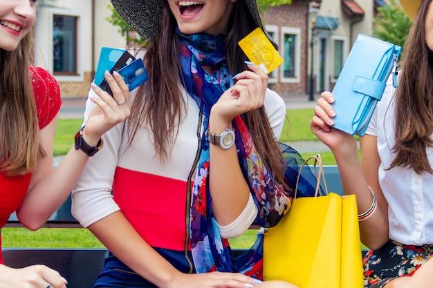 De gelukkige kleurrijke vrienden van de volwassenenmeisjes van vrouwenvrouwen in kleurrijke kleding openlucht zitten alvorens met creditcards in winkelcomplex te winkelen.