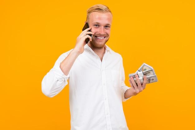 De gelukkige knappe blonde mens in een wit overhemd houdt een bundel van papiergeldnota's en sprekend op de telefoon op geel