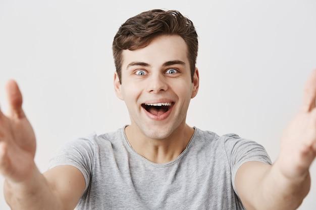 De gelukkige knappe europese kerel glimlacht gelukkig aangezien hij prettige woorden van ouders ontvangt, witte perfecte tanden toont, zijn armen voor camera strekkend. de jonge mannelijke student verheugt zich succesvolle dag
