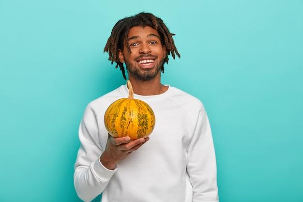 De gelukkige knappe jonge kerel van gemengd ras met dreadlocks, houdt weinig rijpe gele pompoen vast, die dieetsalade gaat maken, gekleed in vrijetijdskleding