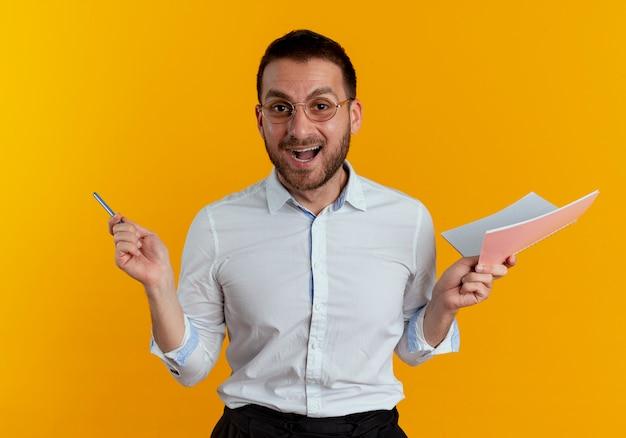 De gelukkige knappe mens met optische bril houdt pen en notitieboekje dat op oranje muur wordt geïsoleerd