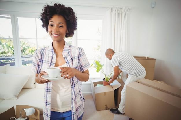 De gelukkige kop van de vrouwenholding in de woonkamer