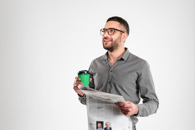 De gelukkige krant van de zakenmanlezing het drinken koffie