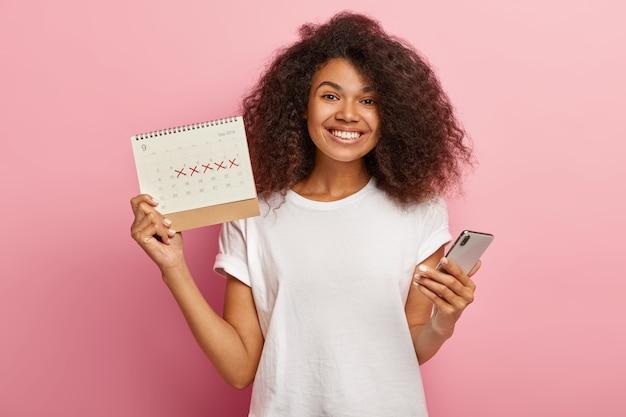 De gelukkige krullende vrouw houdt periodekalender