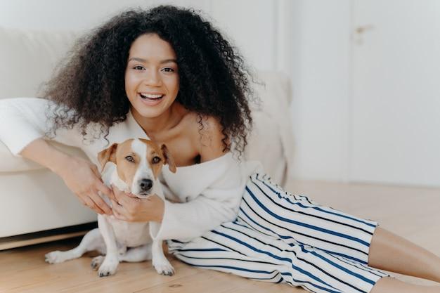 De gelukkige krullende vrouw speelt met grappige kleine hond, stelt op vloer in ruime ruimte, dichtbij bank, glimlacht breed, omhelst huisdier met liefde