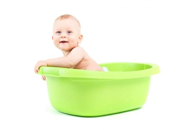 De gelukkige leuke babyjongen neemt bad in groene ton