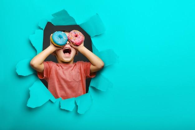 De gelukkige leuke jongen heeft pret die met donuts op zwarte muur wordt gespeeld als achtergrond. heldere foto van een kind.