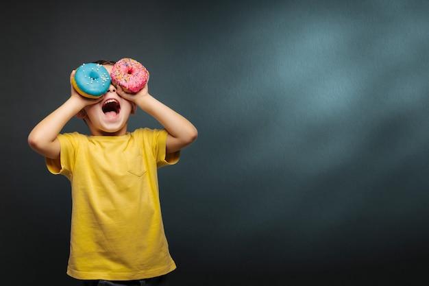 De gelukkige leuke jongen heeft pret die met donuts op zwarte muur wordt gespeeld als achtergrond.