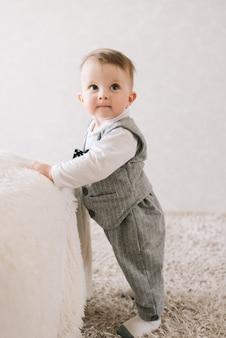 De gelukkige leuke jongen in het kostuum van een heer bevindt zich dichtbij de steun op een lichte achtergrond, proberend op te staan, lerend te lopen.