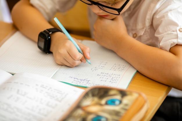 De gelukkige leuke slimme jongen zit bij een bureau in glazen met het opheffen van hand.