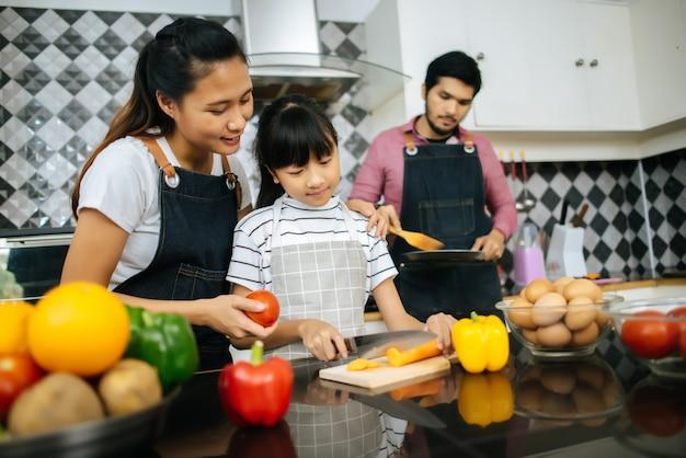 De gelukkige mama onderwijst haar dochter die groente hakt die ingrediënten voorbereidt