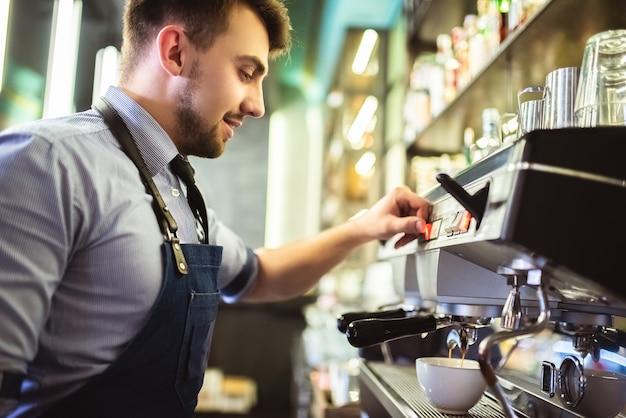 De gelukkige man die koffie maakt aan de bar