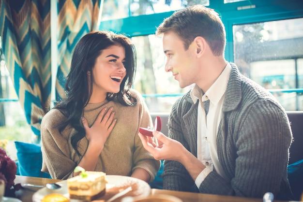 De gelukkige man doet een voorstel aan zijn vriendin in het restaurant