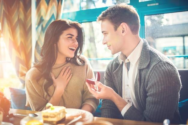 De gelukkige man doet een voorstel aan zijn vrouw in het restaurant