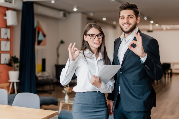 De gelukkige man en de vrouw in het bureau tonen ok gebaar