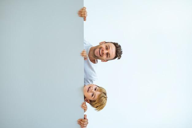 De gelukkige man en een jongen die achter de muur staan