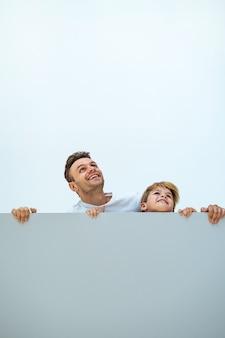 De gelukkige man en een jongen staan achter de muur