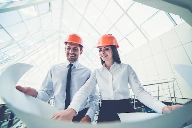 De gelukkige man en vrouw in een helm houden het projectplan in het gebouw vast