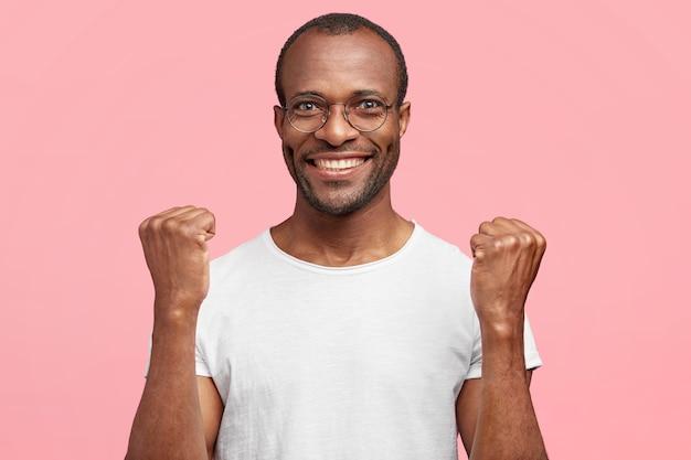 De gelukkige man klemt zijn tanden en vuisten, heeft brede glimlach, verheugt zich over zijn triomf, geïsoleerd over roze muur