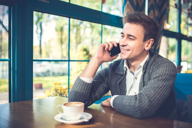De gelukkige man met een kopje koffie telefoon in het restaurant