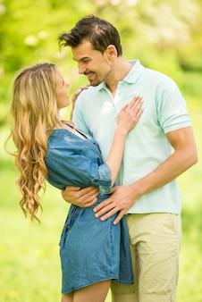 De gelukkige man omhelst een vrouw in een mooi hout.