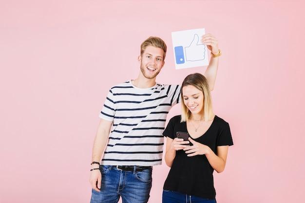 De gelukkige manholding beduimelt omhoog gebaar over vrouw gebruikend cellphone