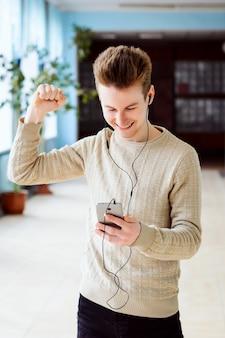 De gelukkige mannelijke student stijgt omhoog zijn hand terwijl het kijken aan mobiele telefoon