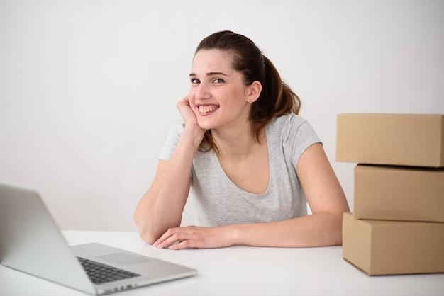 De gelukkige meisjesexploitant zit voor laptop die alle bestellingen en alle leveringen heeft voltooid