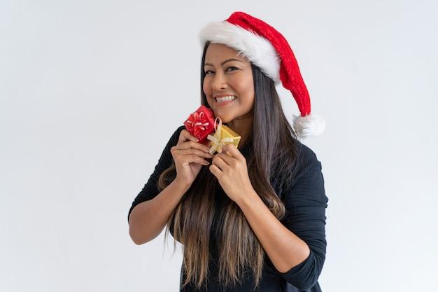 De gelukkige mengeling rent vrouw die over de giften van kerstmis wordt opgewekt