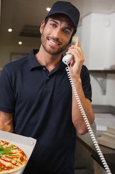 De gelukkige mens die van de pizzalevering een orde over de telefoon nemen