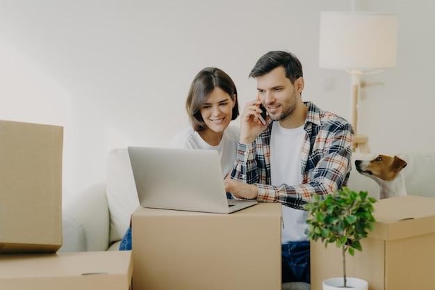 De gelukkige mens doorbladert laptop in nieuwe flat, roept via smartphone, beweegt samen met vrouw in nieuw appartement