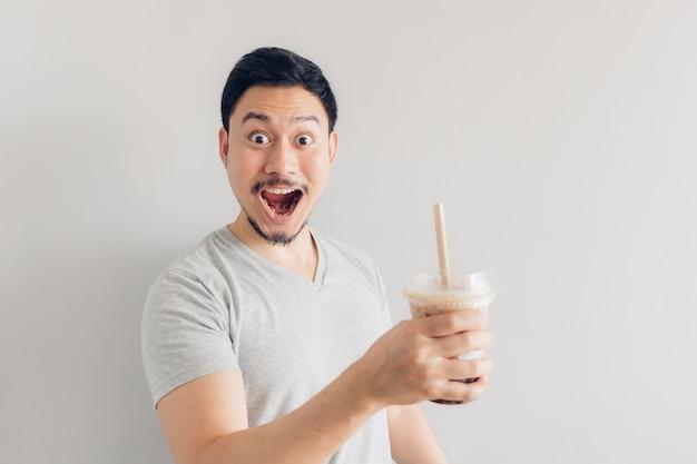 De gelukkige mens drinkt de thee van de bellenmelk of de thee van de parelmelk. populaire melkthee in azië en taiwan.
