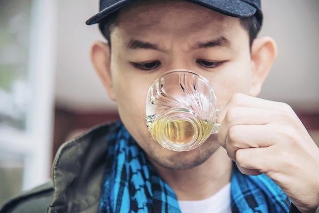 De gelukkige mens drinkt hete theekop - de aziatische mensen met hete theedrank ontspant concept