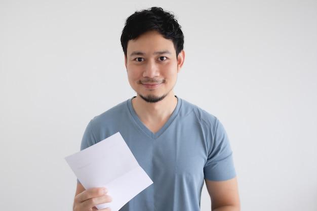 De gelukkige mens houdt een factuurbrief op geïsoleerde witte muur.