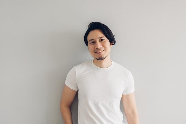 De gelukkige mens van het glimlachgezicht met lang zwart haar en wit t-shirt.